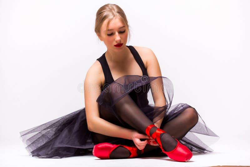 Stående av den unga ballerinabalettdansören som binder häftklammermatare runt om hennes ben fotografering för bildbyråer