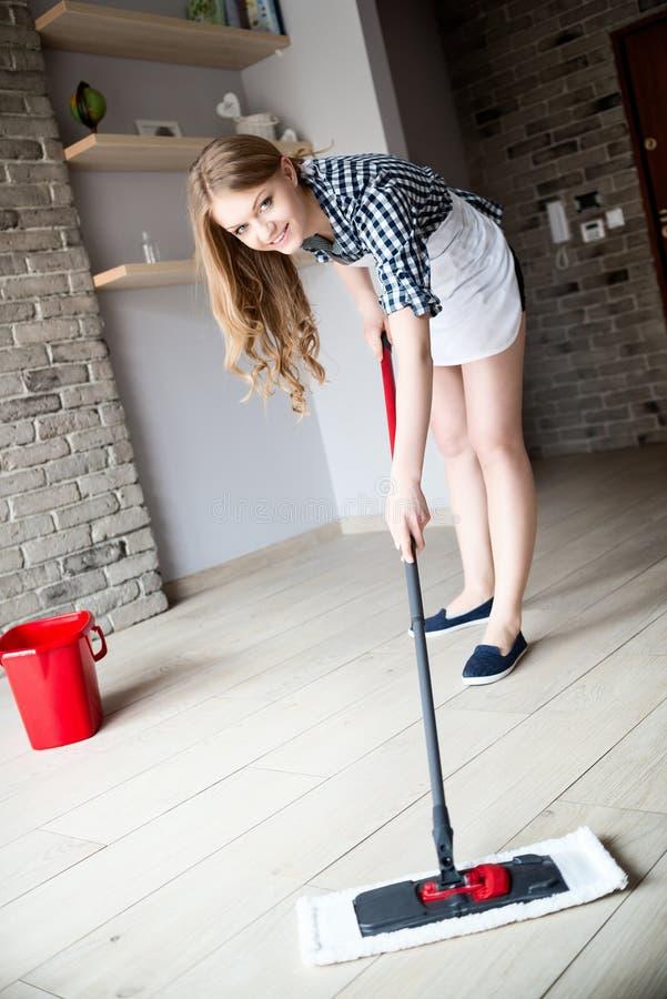 Stående av den unga blonda kvinnan som moppar golvet royaltyfri bild