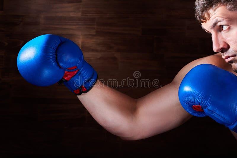 Stående av den unga boxarekämpen med boxninghandskar mot träväggen fotografering för bildbyråer