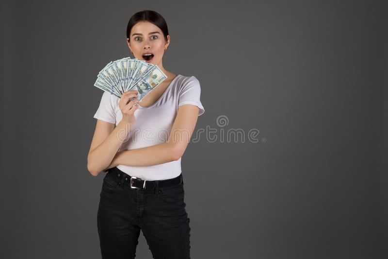 Stående av den unga brunettkvinnan i whotet-skjortan som rymmer sedlar och att fira för pengar arkivbild