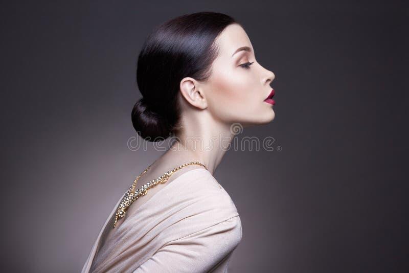 Stående av den unga brunettkvinnan mot en mörk bakgrund Mystisk ljus bild av en kvinna med yrkesmässig makeup royaltyfri foto