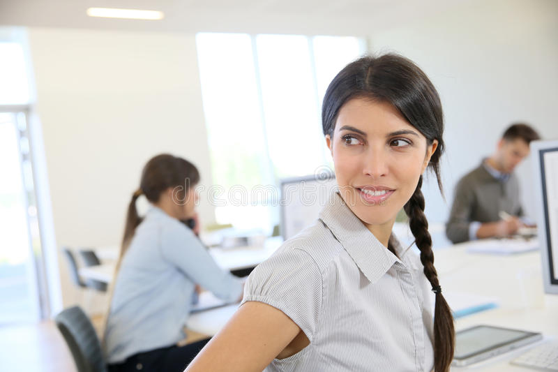 Stående av den unga brunettkvinnan som arbetar på kontoret royaltyfri bild
