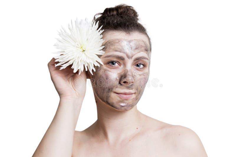 Stående av den unga caucasian kvinnan med den svarta kosmetiska framsidamaskeringen som isoleras på vit bakgrund Föryngra hud av  fotografering för bildbyråer