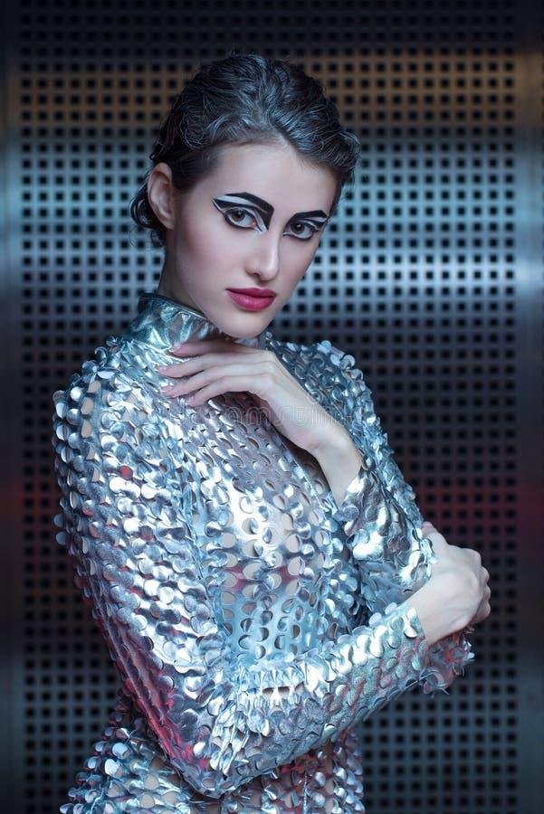 Stående av den unga cyberkvinnan i futuristisk dräkt för silver med ljus makeup arkivfoton