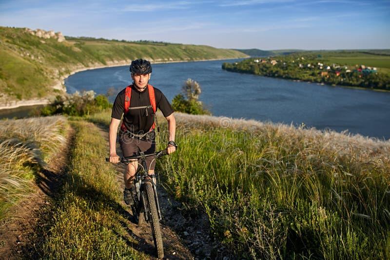 Stående av den unga cyklistridningmountainbiket som är stigande ovanför den härliga blåa floden fotografering för bildbyråer