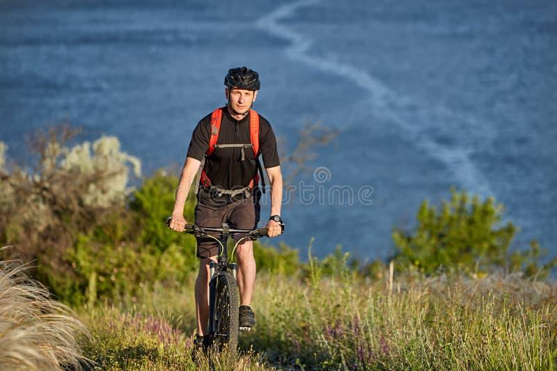 Stående av den unga cyklistridningmountainbiket som är stigande ovanför den härliga blåa floden arkivfoto