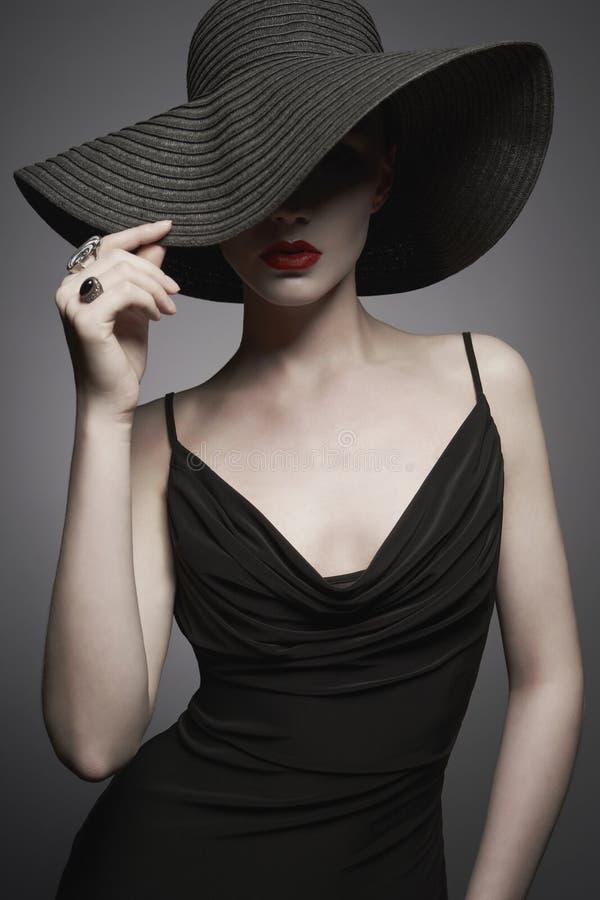 Stående av den unga damen med den svarta hatten och aftonklänningen fotografering för bildbyråer