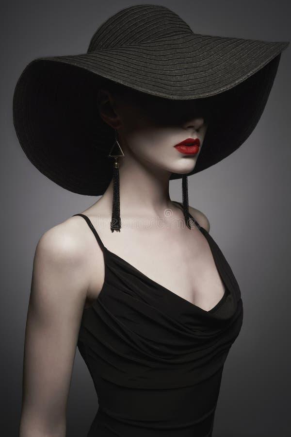 Stående av den unga damen med den svarta hatten och aftonklänningen royaltyfria foton