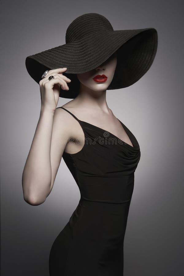 Stående av den unga damen med den svarta hatten och aftonklänningen arkivfoto
