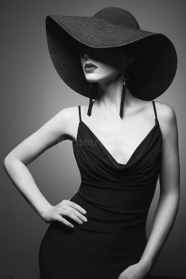 Stående av den unga damen med den svarta hatten och aftonklänningen royaltyfri fotografi