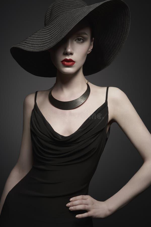 Stående av den unga damen med den svarta hatten och aftonklänningen royaltyfria bilder