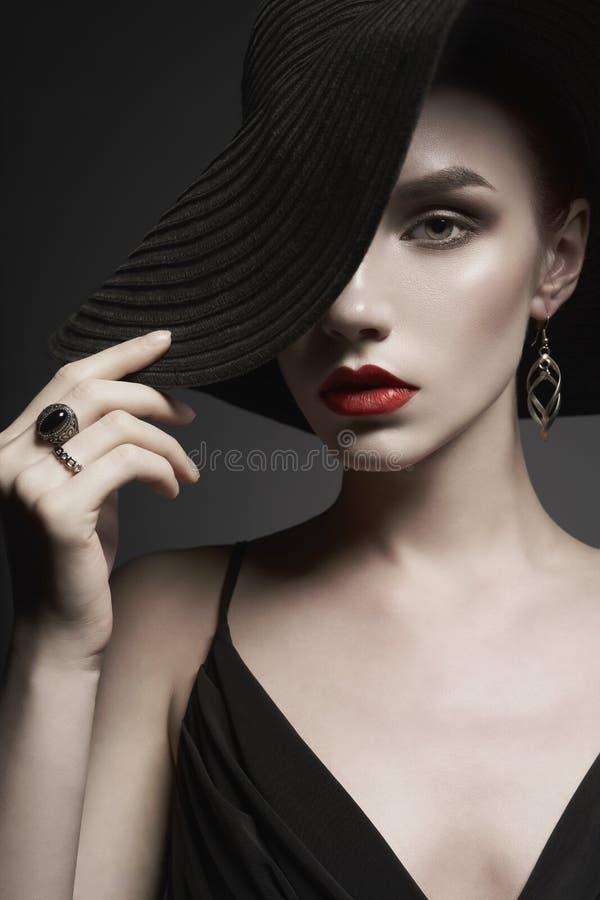 Stående av den unga damen med den svarta hatten och aftonklänningen arkivbild