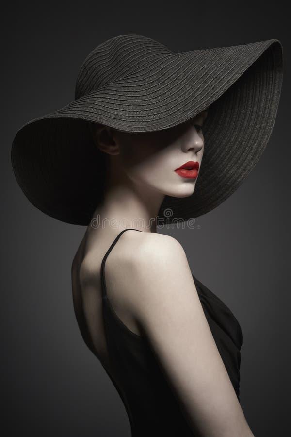 Stående av den unga damen med den svarta hatten och aftonklänningen royaltyfri bild