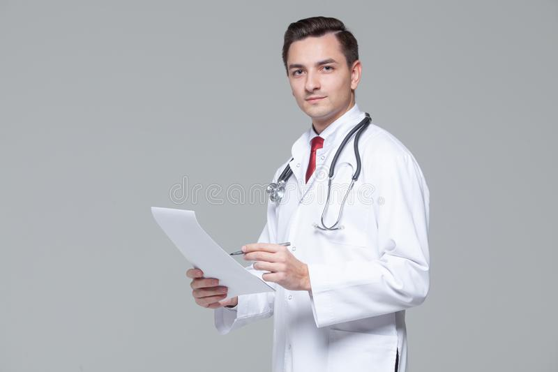 St?ende av den unga doktorn i den vita likformign med stetoskopinnehavmappen arkivbild