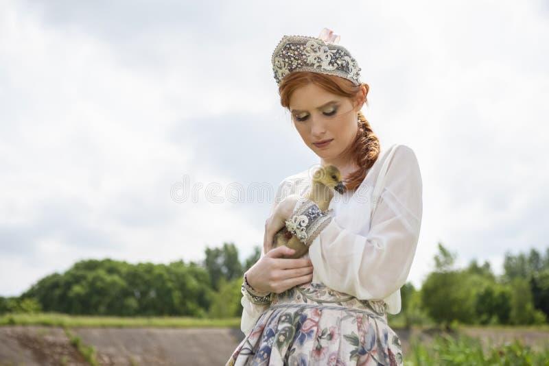 Stående av den unga försiktiga caucasian flickan som poserar den hållande ankungen i rysk stilklänning och Kokoshnik det fria royaltyfri fotografi