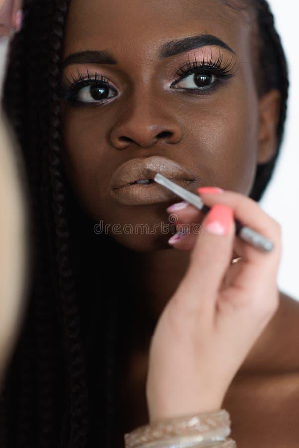 Stående av den unga förtjusande afrikanska damen som mottar det yrkesmässiga sminket Konstnären applicerar läppstift royaltyfria bilder