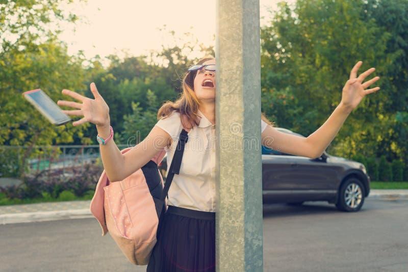 Stående av den unga frånvarande flickan som distraheras av mobiltelefonen Flickan kraschade in i gatastolpen, tappad telefon royaltyfri bild