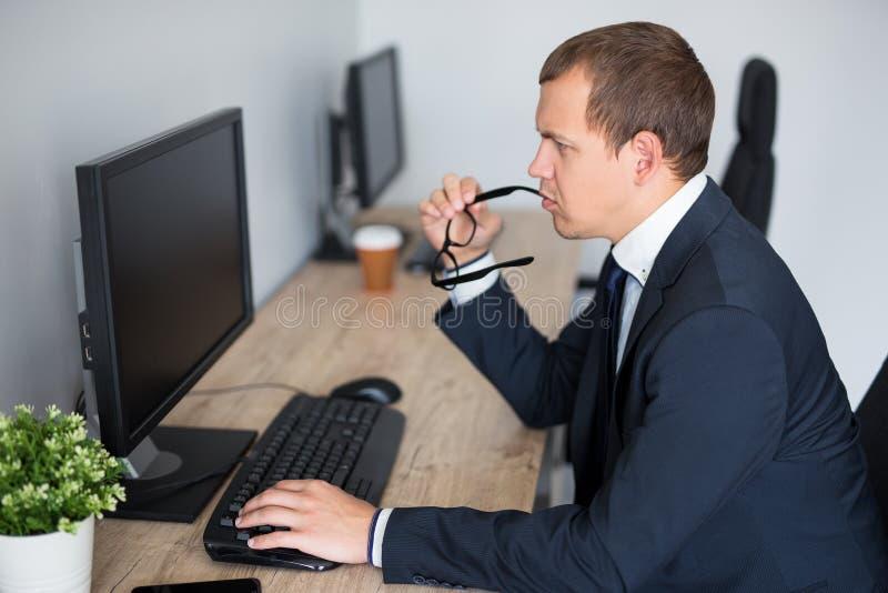St?ende av den unga fundersamma aff?rsmannen som anv?nder datoren i det moderna kontoret - tom sk?rm med kopieringsutrymme royaltyfria bilder