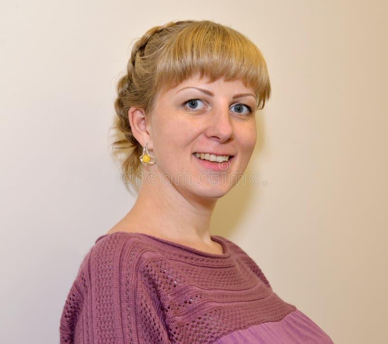 Stående av den unga glade kvinnan med bärnstensfärgade örhängen royaltyfria foton