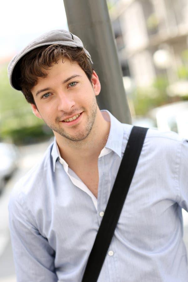 Stående av den unga gladlynta mannen med hatten royaltyfria bilder