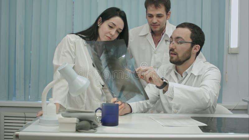Stående av den unga gruppen av doktorer som ser röntgenstrålen royaltyfria bilder