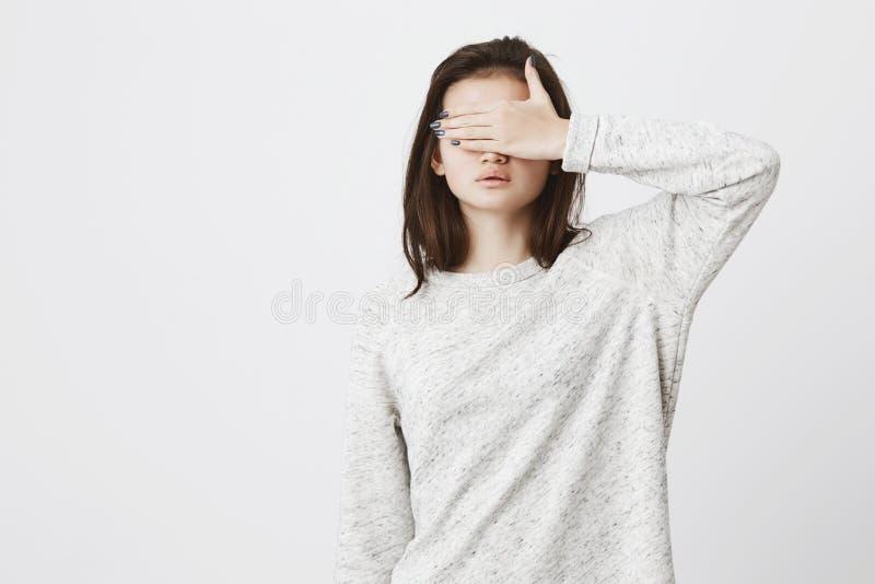 Stående av den unga gulliga brunetten i moderiktig kläder och att täcka henne ögon med handen som står över den vita väggen Sinne royaltyfri bild