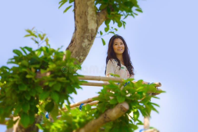 Stående av den unga härliga asiatiska koreanska kvinnan som tycker om sikten från hög synvinkel i le för träd som är lyckligt och arkivbild