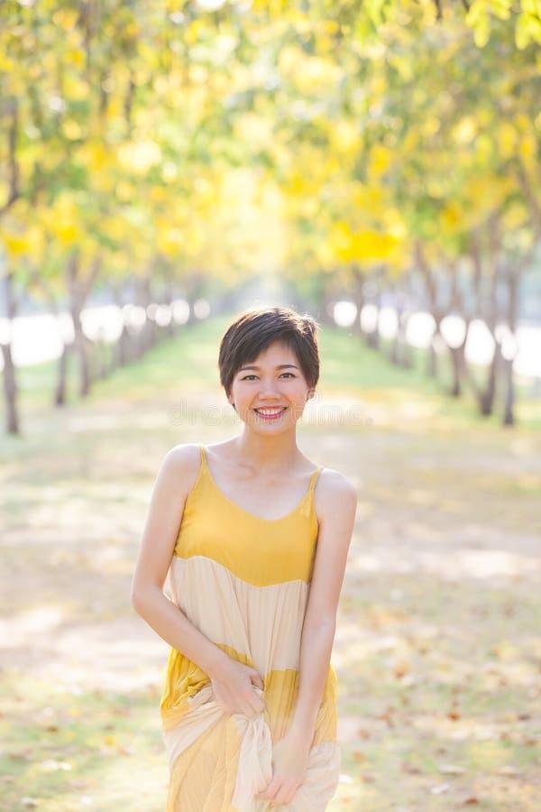 Stående av den unga härliga asiatiska kvinnan som bär gula långa dres fotografering för bildbyråer