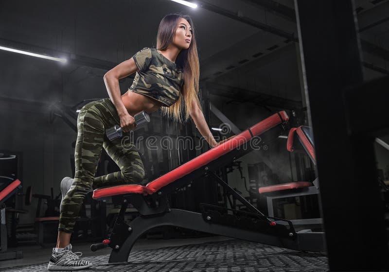 Stående av den unga härliga asiatiska kvinnan som utarbetar på idrottshallen royaltyfria bilder