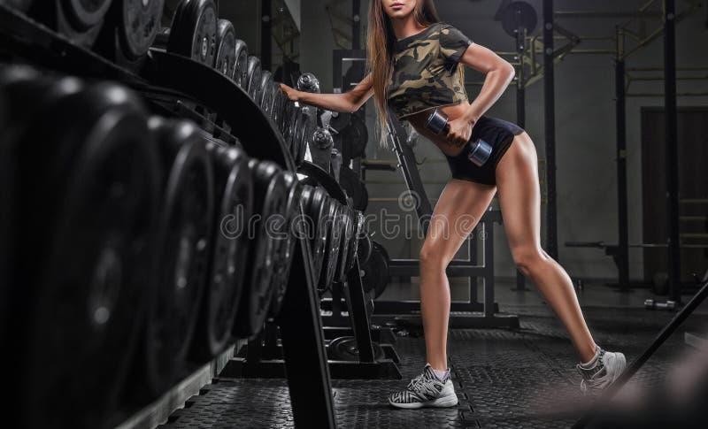 Stående av den unga härliga asiatiska kvinnan som utarbetar på idrottshallen arkivbilder