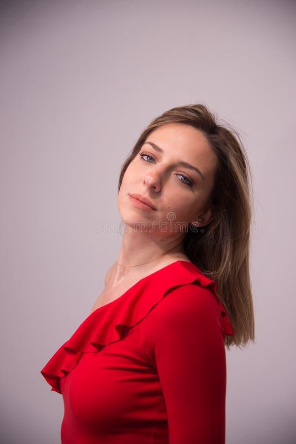 Stående av den unga härliga blonda flickan i studio på vit royaltyfria bilder