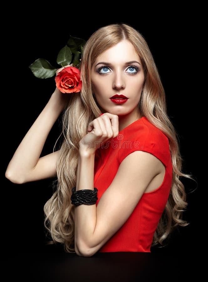 Stående av den unga härliga blonda kvinnan i röd klänning med rött r arkivbild