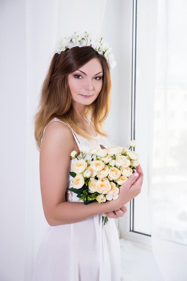 Stående av den unga härliga bruden i den vita klänningen med blommast arkivbilder