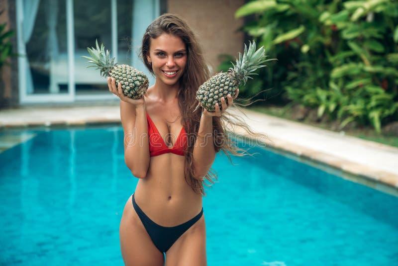 Stående av den unga härliga brunettflickan i baddräkt med ananas i hennes handfrukt som är hållande på det sexiga bröstet royaltyfri bild