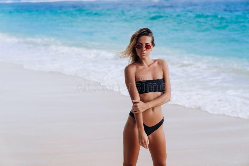 Stående av den unga härliga europeiska kvinnan i baddräkten och solglasögon som står på havstranden arkivfoto