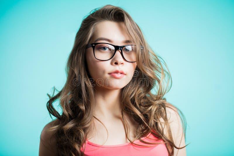 Stående av den unga härliga flickan över blå bakgrund royaltyfri foto