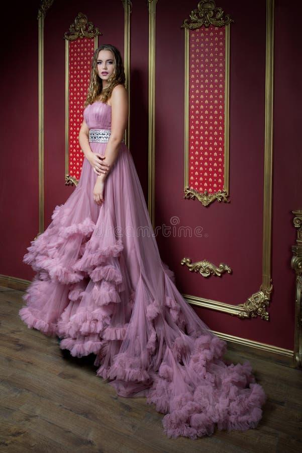 Stående av den unga härliga flickan i den rika inre royaltyfria foton