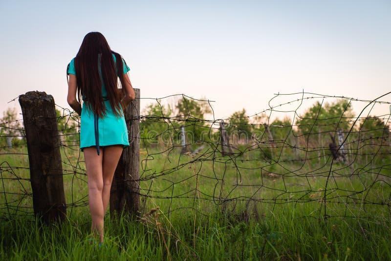 Stående av den unga härliga flickan i en turkosklänning nära taggtråd i utomhus- sommar arkivbild