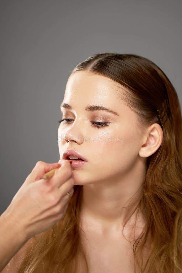Stående av den unga härliga flickan i studio, med yrkesmässig makeup Skönhetskytte Makeupkonstnären målar hennes kanter med arkivbilder