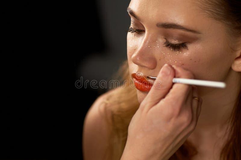 Stående av den unga härliga flickan i studio, med yrkesmässig makeup Skönhetskytte Makeupkonstnären målar hennes kanter med arkivfoto