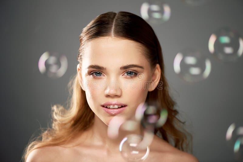 Stående av den unga härliga flickan i studio, med yrkesmässig makeup Skönhetskytte Skönheten av såpbubblor _ royaltyfri fotografi