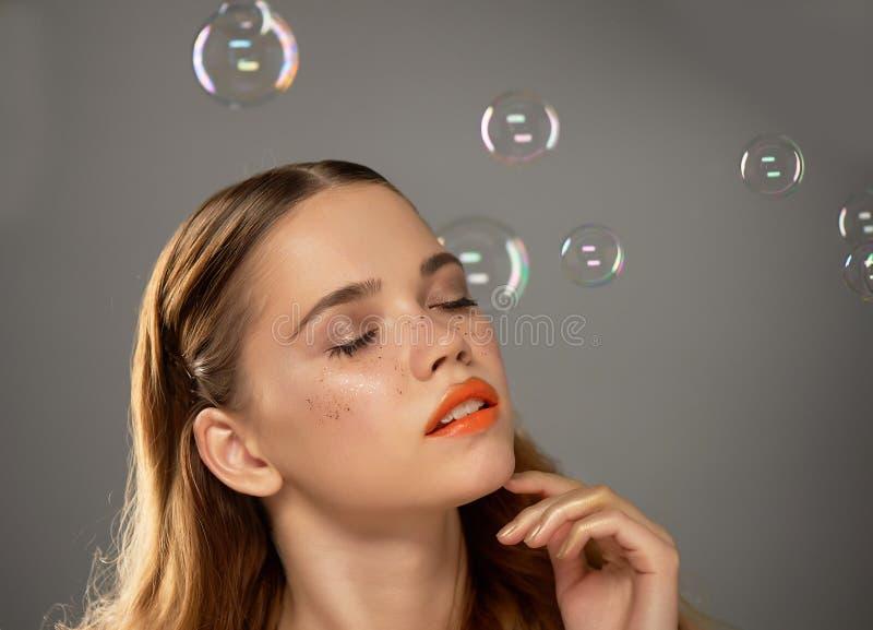 Stående av den unga härliga flickan i studio, med yrkesmässig makeup Skönhetskytte Skönheten av såpbubblor _ arkivbild