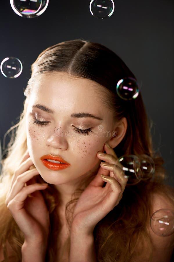 Stående av den unga härliga flickan i studio, med yrkesmässig makeup Skönhetskytte Skönheten av såpbubblor _ arkivbilder