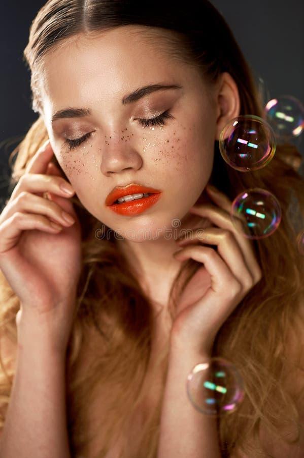 Stående av den unga härliga flickan i studio, med yrkesmässig makeup Skönhetskytte Skönheten av såpbubblor _ royaltyfria bilder