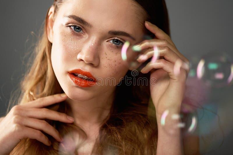 Stående av den unga härliga flickan i studio, med yrkesmässig makeup Skönhetskytte Skönheten av såpbubblor _ royaltyfri foto