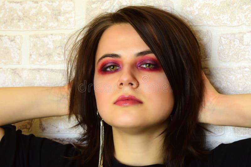 Stående av den unga härliga flickan med gröna ögon och ett ljust idérikt smink i lila signaler fotografering för bildbyråer