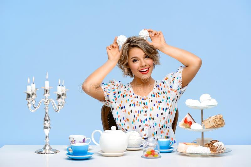 Stående av den unga härliga flickan med sötsaker över blå bakgrund arkivbilder