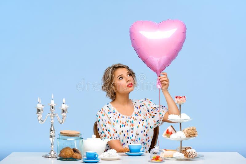 Stående av den unga härliga flickan med sötsaker över blå bakgrund royaltyfria bilder