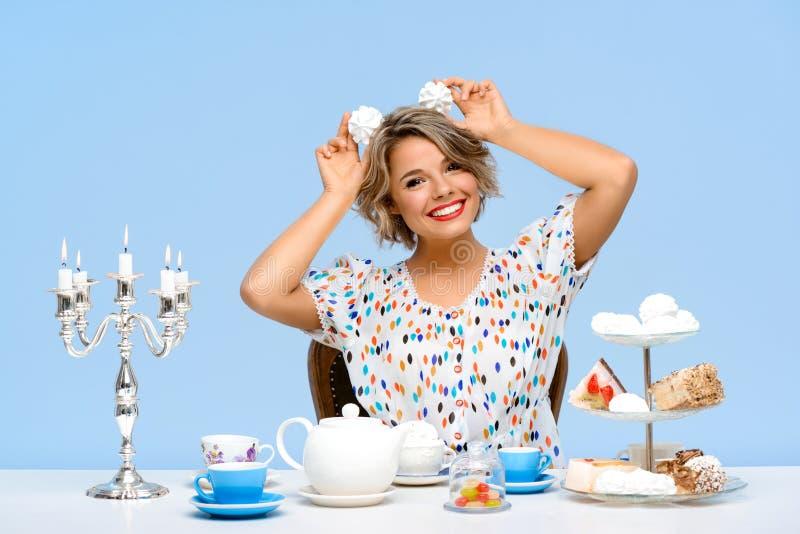 Stående av den unga härliga flickan med sötsaker över blå bakgrund royaltyfri bild