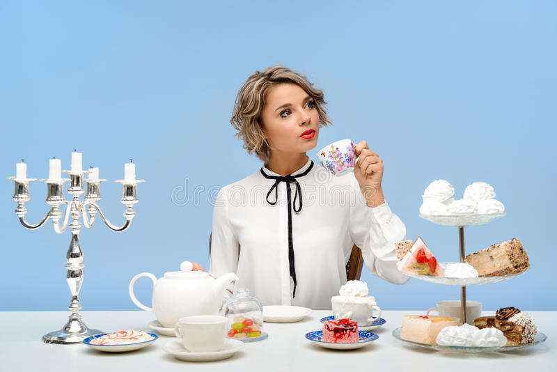 Stående av den unga härliga flickan med sötsaker över blå bakgrund arkivbild